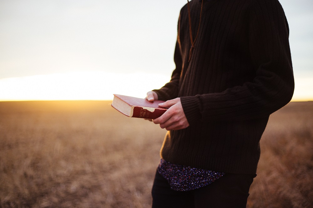 Holding Bible in Field